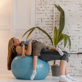 Mujer de tiro completo y niño en bola de gimnasio