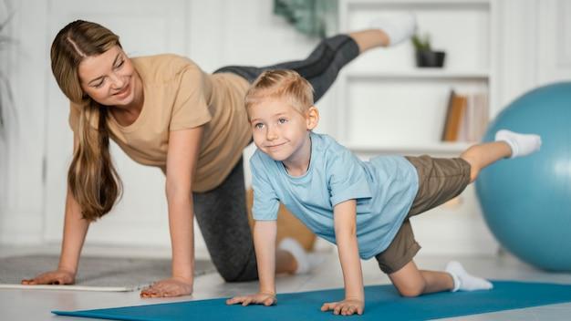 Mujer de tiro completo y niño haciendo ejercicio juntos