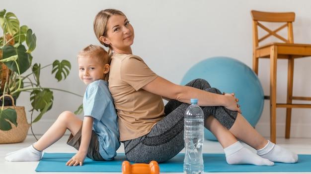 Mujer de tiro completo y niño posando juntos
