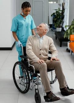 Mujer de tiro completo y paciente en silla de ruedas