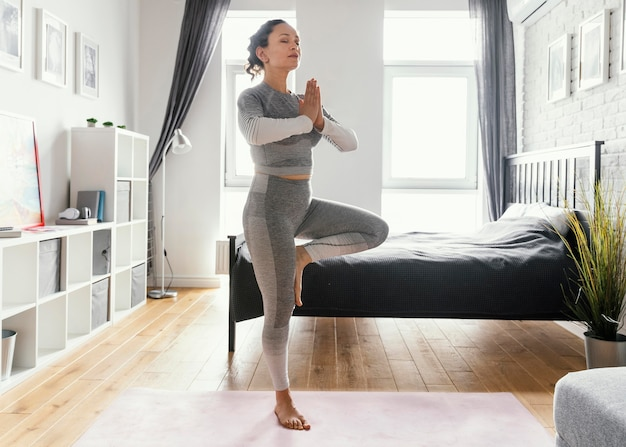 Mujer de tiro completo de pie sobre una pierna