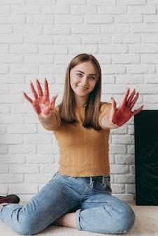 Mujer de tiro completo con pintura en las manos