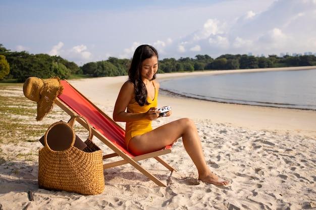 Mujer de tiro completo en la playa en silla