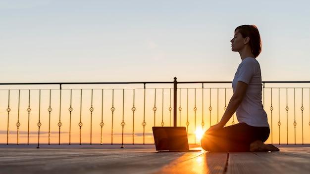 Mujer de tiro completo con portátil meditando