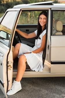 Mujer de tiro completo posando en coche
