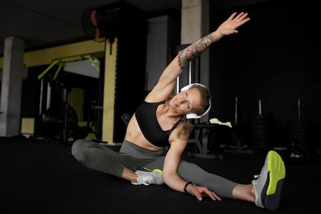 Mujer de tiro completo que se extiende en el gimnasio
