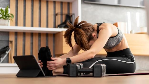 Mujer de tiro completo que se extiende sobre la alfombra