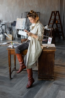 Mujer de tiro completo en silla con tableta