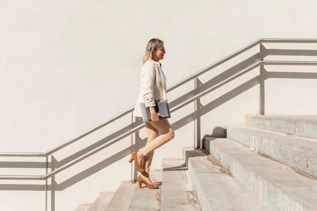 Mujer de tiro completo subiendo escaleras
