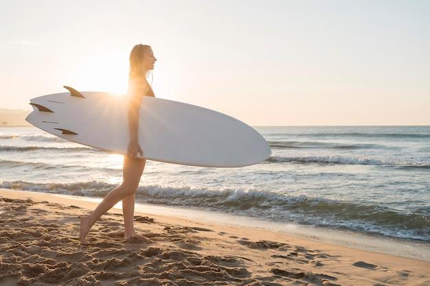 Mujer de tiro completo con tabla de surf