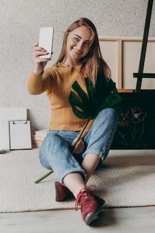 Mujer de tiro completo tomando selfie