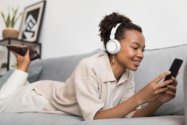Mujer de tiro completo usando audífonos