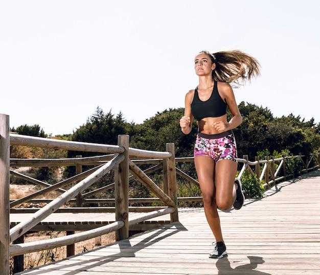 Mujer de tiro largo corriendo en el muelle