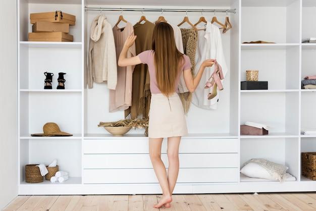 Mujer de tiro largo mirando a través de su ropa