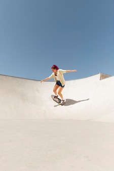 Mujer de tiro largo en patineta fuera