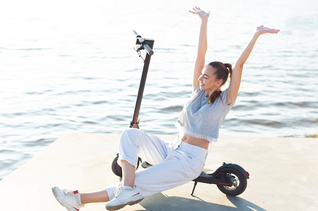 Mujer de tiro largo posando en scooter con sus manos arriba