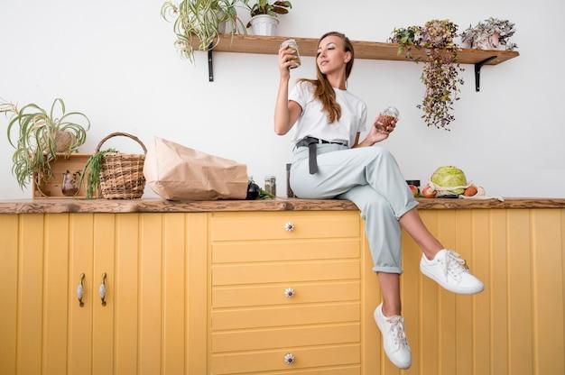 Mujer de tiro largo posando sobre una encimera de cocina
