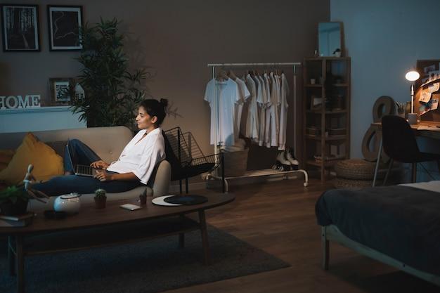 Mujer de tiro largo que trabaja en la computadora portátil desde casa