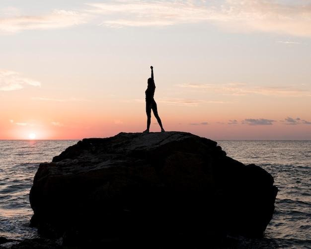 Mujer de tiro largo en ropa deportiva disfrutando de la puesta de sol