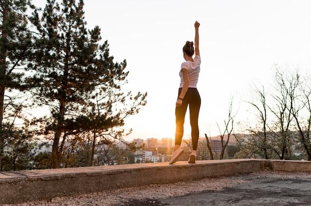 Mujer de tiro largo en ropa deportiva siendo victoriosa