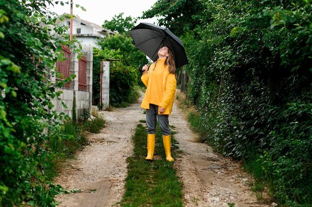 Mujer de tiro largo en ropa de lluvia sosteniendo un paraguas