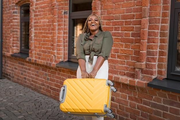 Mujer de tiro largo tratando de levantar un pesado equipaje amarillo