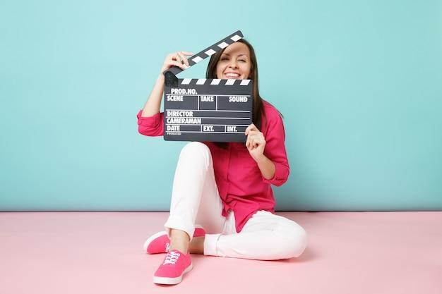 Mujer de tiro de longitud completa en pantalones blancos de camisa rosa sentada en el piso con claqueta de cine
