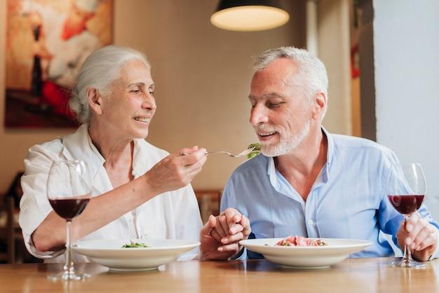 Mujer de tiro medio alimentando a su esposo en el restaurante