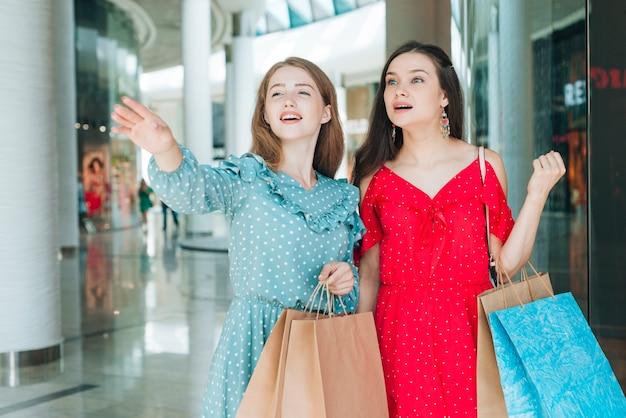 Mujer de tiro medio apuntando lejos en el centro comercial