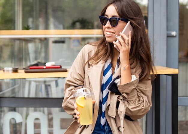 Mujer de tiro medio bebiendo limonada y hablando por teléfono