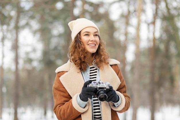 Mujer de tiro medio con cámara de fotos
