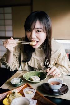 Mujer de tiro medio comiendo con palillos