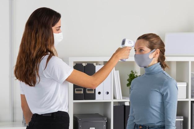 Mujer de tiro medio comprobando la temperatura