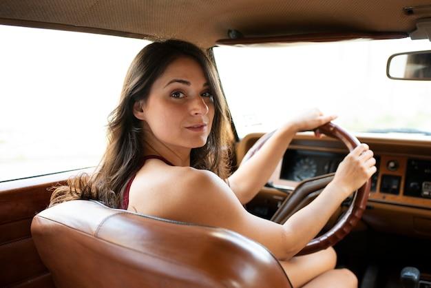 Mujer de tiro medio conduciendo coche