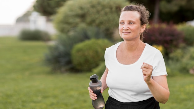 Mujer de tiro medio corriendo al aire libre