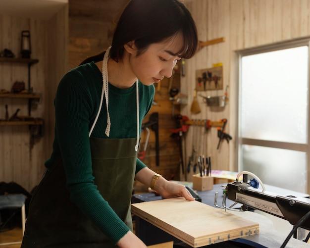 Mujer de tiro medio cortando madera