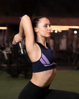 Mujer de tiro medio ejercicio con mancuernas