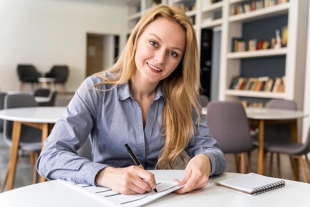 Mujer de tiro medio escribiendo