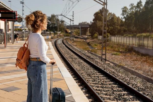 Mujer de tiro medio esperando en la estación de tren