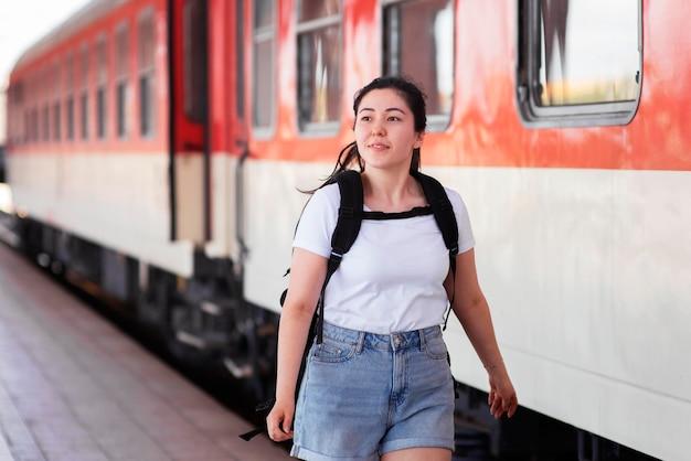 Mujer de tiro medio en la estación de tren
