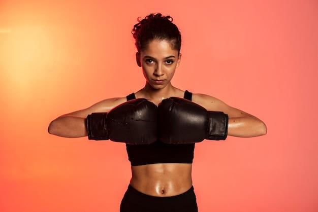 Mujer de tiro medio con guantes de boxeo
