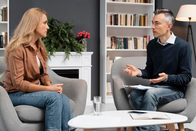 Mujer de tiro medio hablando con consejero de hombre