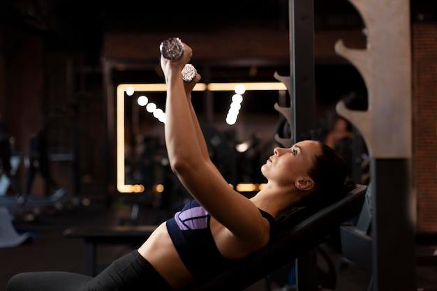Mujer de tiro medio levantando pesas
