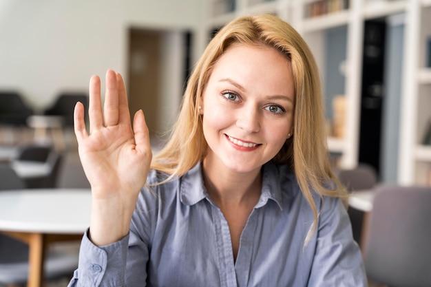 Mujer de tiro medio con la mano arriba