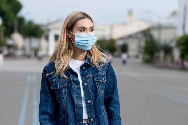 Mujer de tiro medio con máscara médica