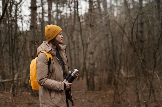 Mujer de tiro medio con matraz al aire libre