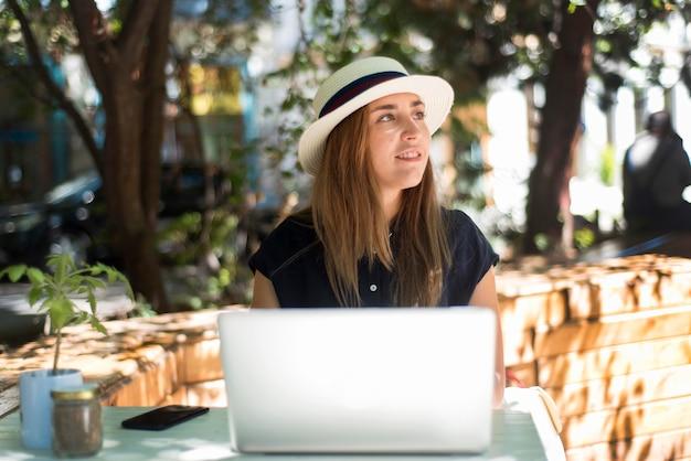 Mujer de tiro medio en la mesa usando laptop