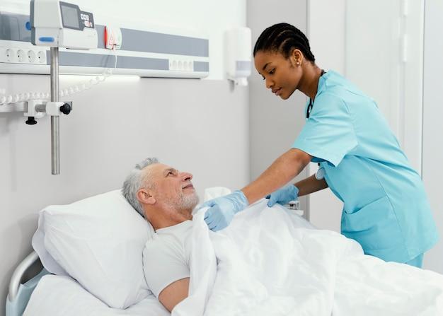 Mujer de tiro medio metiendo al paciente en la cama