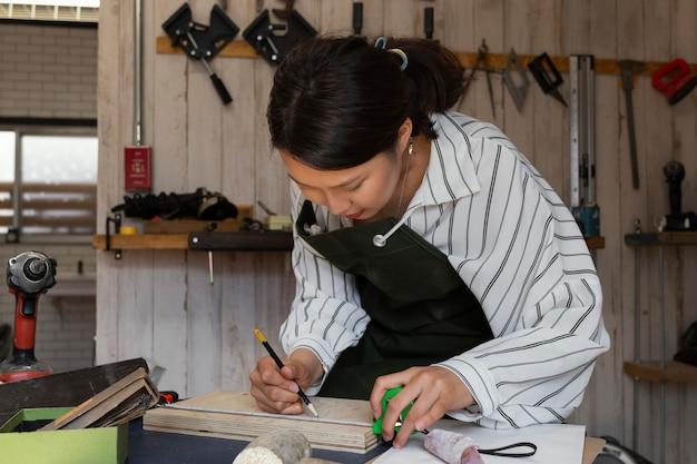 Mujer de tiro medio midiendo madera
