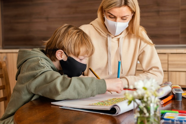 Mujer de tiro medio y niño con máscara